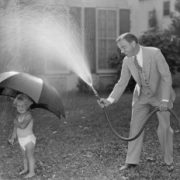 A man spraying a hose at a little kid with an umbrella