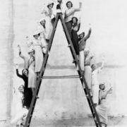 A bunch of people standing on both sides of a ladder waving