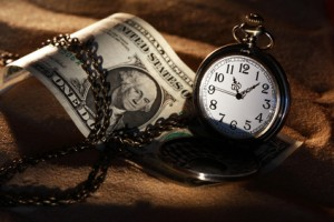 An old pocket watch with a dollar bill right next to it.