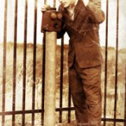 A man, standing by a iron fence talking on a phone