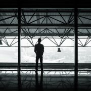 Man standing on an upper floor of an open air building looking out onto a tarmac with an airplane.