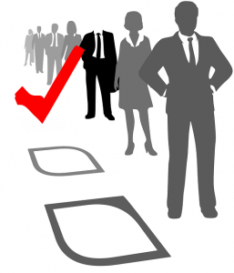 Illustration of business people, in gray suites, standing in a line next to boxes on the ground. A big red checkmark is beside the business person in a black suite.