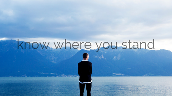 Person, dressed in black, standing in front of a blue lake with mountains on the other side of the lake. Title - know where you stand