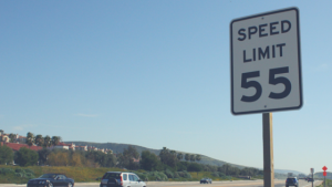 Speed limit sign along a highway. Sign reads 55.
