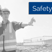 Two guys in safety vests and hard hats with a clipboard pointing at something on a worksite. Title - Safety Pays