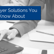hand using the mouse on a laptop with papers on same table and a pen on top of papers. Pearls hanging from the person's neck tough the table with title - 3 Employer Solutions You Should Know About