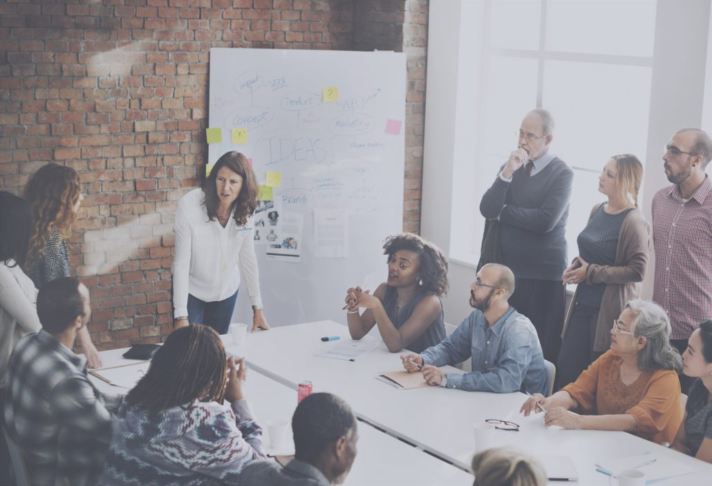 Group of people sitting at a large conference table with a whiteboard in the background. A boss seems to be training them.