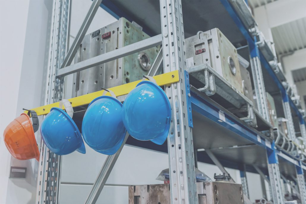 Four hard hats hung on a shelf next to some manufactured parts.