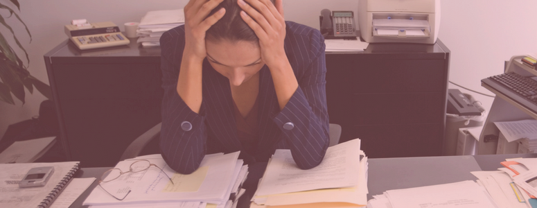 woman in business suit holds her head in her hands with frustration. she is leaned on her disk with piles of paperwork