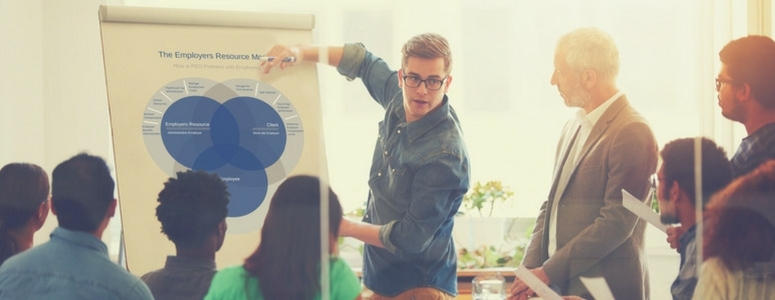 image of man presenting to group of people. He is pointing to a board with a graph image on it of the employers resource model