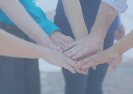 image of five people putting their hands together in a huddle. Image has a blue tint over the picture