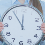 image is of a woman holding a wall clock in front of her. the time shows 11:54