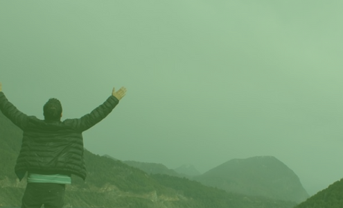 image of man standing in front of foggy mountains with arms stretched up to the sky