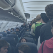 image of people walking in the aisle of a plane and finding their seats. Many people are already sitting. The image has a transparent blue filter over it