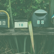 Image of a row of 6 different mailboxes. Behind the mailboxes are plants and foliage.