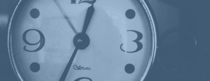 Image of an analog clock set to 12:35. Image has a transparent blue filter over it