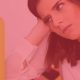 Image of a woman looking frustrated, she is sitting at a table with her head resting on her hand and she is looking at a clock with a yellow border. The clock reads 11:59. The image has a transparent red filter over it.